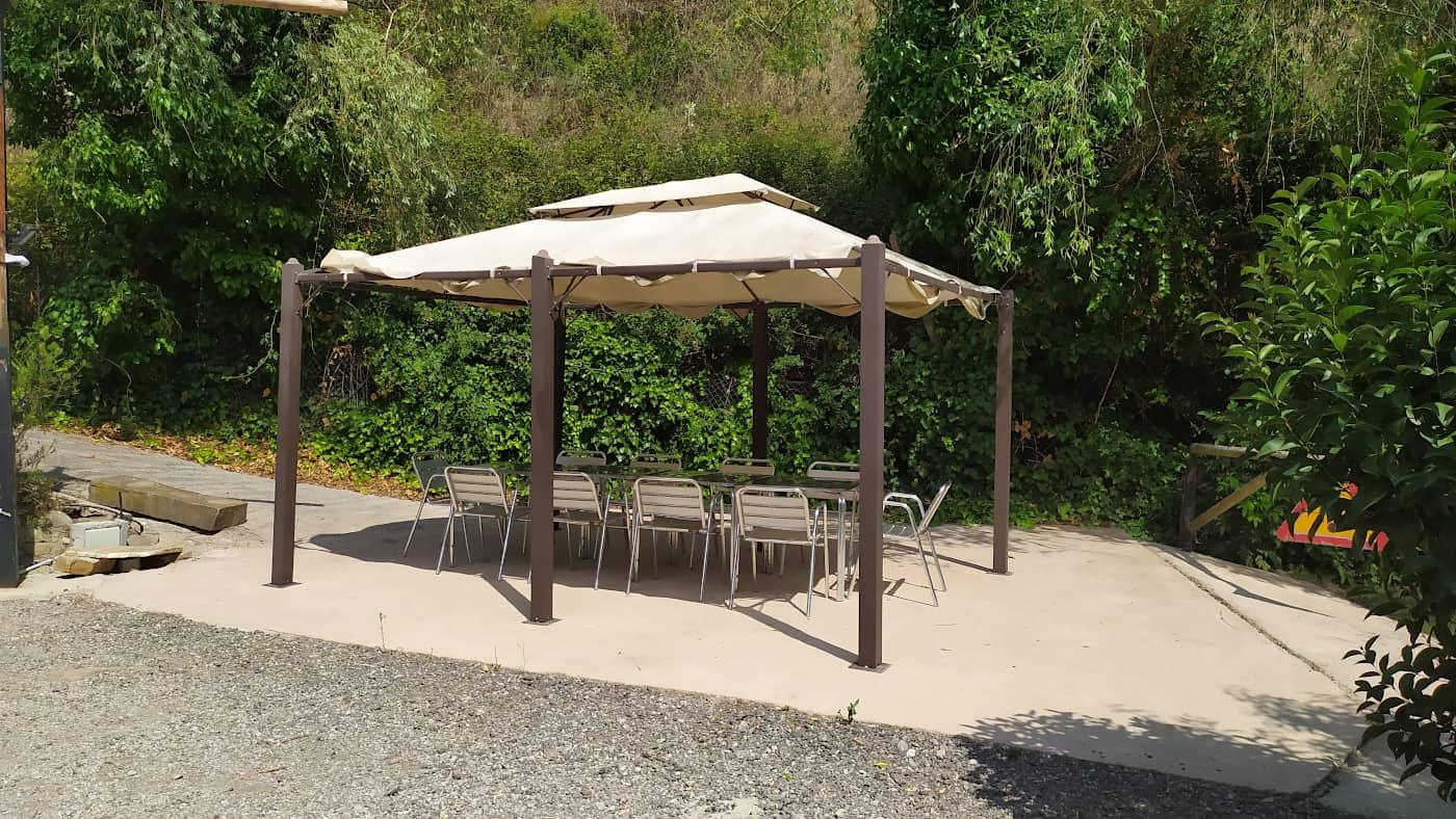 Pèrgola amb taula i cadires per dinar i sopar a l'aire lliure